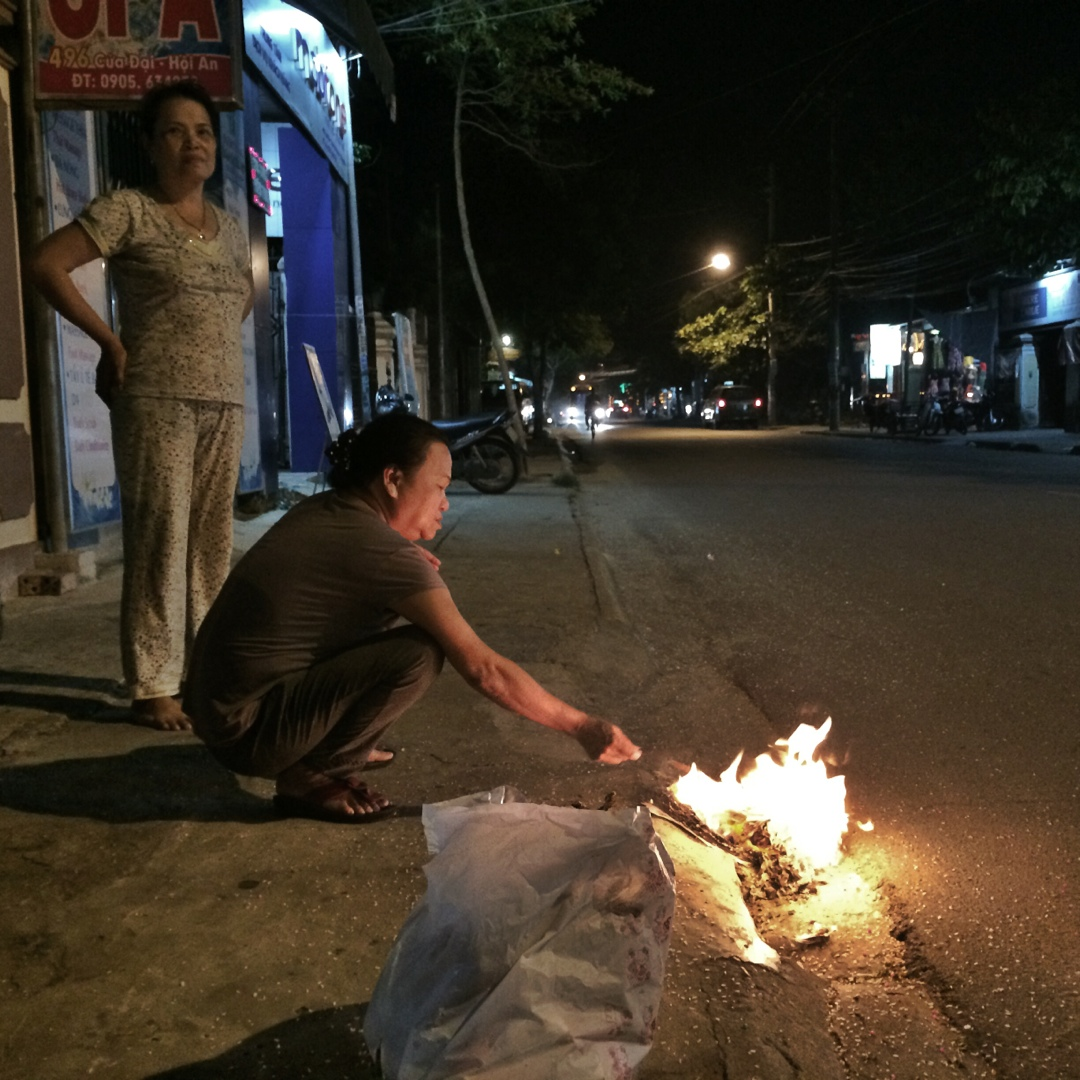 women lighting fire on street
