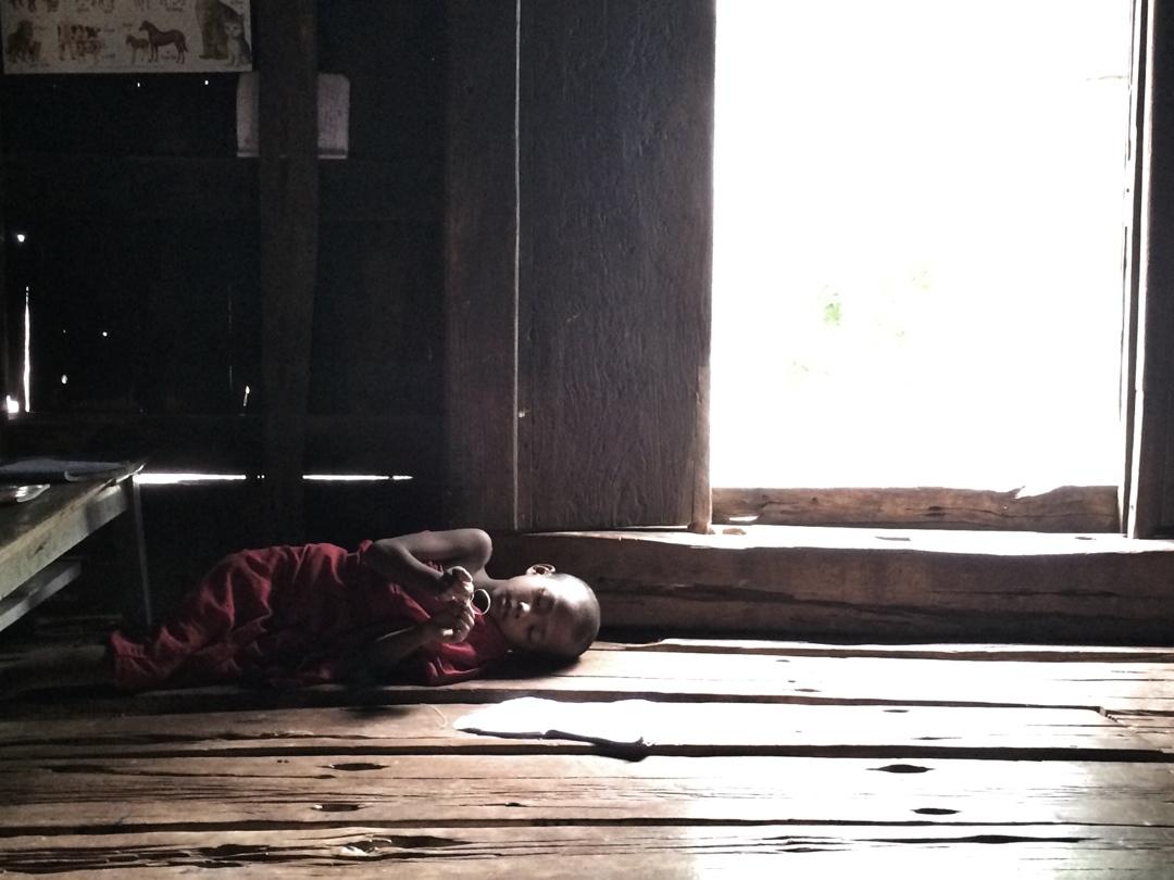 Baby monk lying on floor