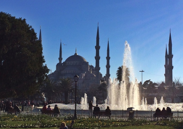 People enjoy the sun at fountain with view at Blue Mosque in Istanbul